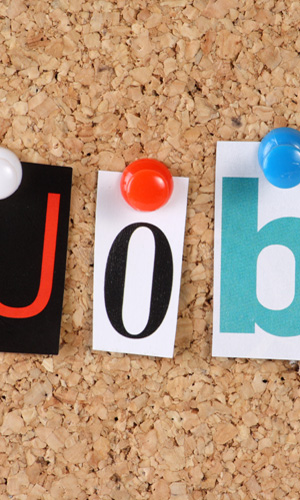 This is a photograph of a cork pin board that has three letters pinned to it that spells the word, jobs. This photograph is linked to the Career site where members can search for a job
