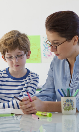 This is a photograph of a female speech pathologist talking to a young boy. It is linked to the What is  Speech Pathologist page on this website