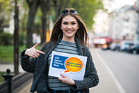This photograph shows a young woman holding a sign with the Speech Pathology Week 2019 logo, as a person needs to do who wants to enter the Speech Pathology Week social media competition.